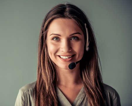 La bella donna di affari in cuffia avricolare sta esaminando la macchina fotografica e sta sorridendo, su fondo grigio