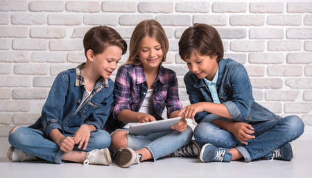 Cute kids are using a digital tablet and smiling while sitting on the floor