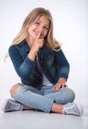 美しい少女は沈黙の兆しを見せ、カメラ目線と明るい背景に床に座って笑顔