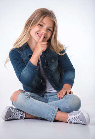 Beautiful little girl is showing silence sign, looking at camera and smiling while sitting on the floor on light background