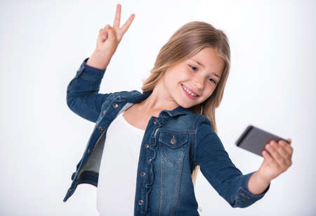 Beautiful little girl is doing selfie using a smart phone, showing peace sign and smiling, on light background Stock Photo