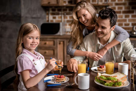 Happy family having breakfast in kitchen. Girl is adding honey to the pancakes while parents are looking at her and smiling Banco de Imagens