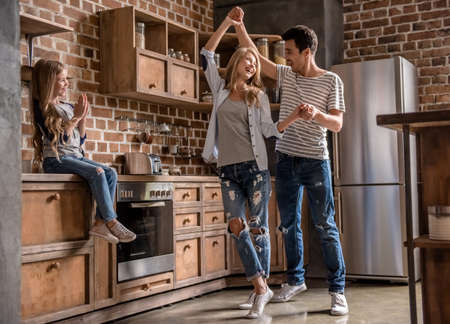 Cute little girl is looking at her beautiful parents dancing, all are smiling while spending time together in kitchen Foto de archivo