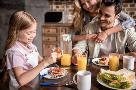 Happy family having breakfast in kitchen. Girl is adding honey to the pancakes while parents are looking at her and smiling Stock Photo