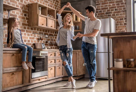 Cute little girl is looking at her beautiful parents dancing, all are smiling while spending time together in kitchen Banque d'images