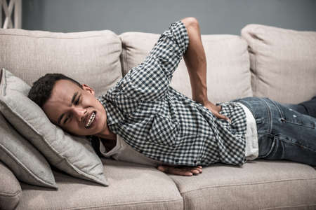 Attractive Afro American guy in casual clothes is touching his back feeling disastrous pain while lying on couch at home