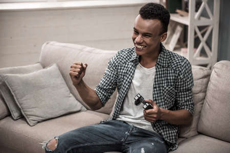 Attractive Afro American guy in casual clothes is playing game console and smiling while sitting on couch at home