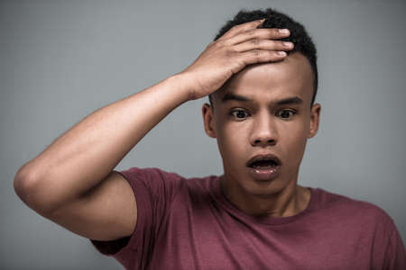 Portrait of attractive Afro American guy touching his forehead and looking with surprise, on gray background