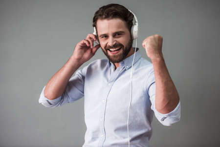 Handsome bearded businessman in smart casual wear and headphones is listening to music, looking at camera and smiling, on gray background