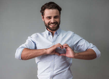 Handsome bearded businessman in smart casual wear is showing a heart, looking at camera and smiling, on gray background Фото со стока
