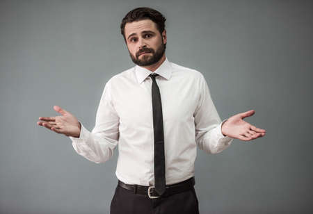 Handsome bearded businessman in formal suit is lifting hands in dismay and looking at camera, on gray background