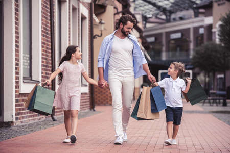 holding hands while walking: Handsome bearded dad and his cute little kids are carrying shopping bags, holding hands and smiling while walking down the street Stock Photo