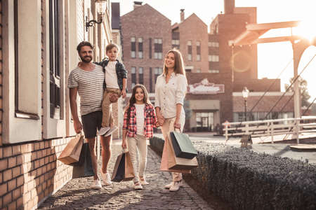 Beautiful parents and their cute little kids are holding shopping bags, looking at camera and smiling while standing outdoors