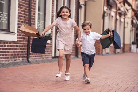 Cute little kids are carrying shopping bags, holding hands and smiling while walking down the street