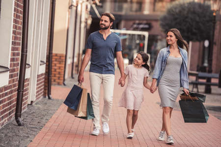 holding hands while walking: Beautiful parents and their cute little daughter are carrying shopping bags, holding hands and smiling while walking down the street Stock Photo