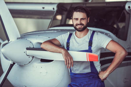 Handsome bearded mechanic in uniform is looking at camera and smiling while leaning on the aircraft in hangar