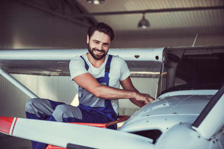 制服を着たハンサムなひげを生やしたメカニックのカメラ目線と格納庫に航空機を修理しながら笑みを浮かべて 写真素材