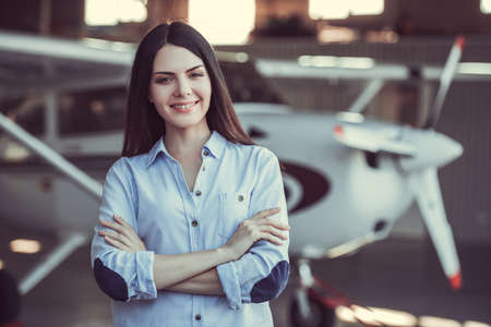 Beautiful woman is looking at camera and smiling while standing with crossed arms near the aircraft in hangar