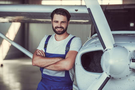 99c32244bb3 Handsome bearded mechanic in uniform is looking at camera and smiling while  leaning on the aircraft