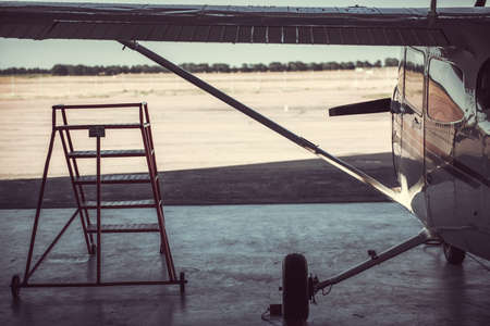A modern white aircraft in hangar, a ladder for a mechanic is near