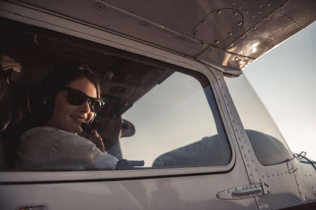 Beautiful woman in aviation headset is looking at camera and smiling while sitting in aircraft ready to fly Фото со стока - 86548325