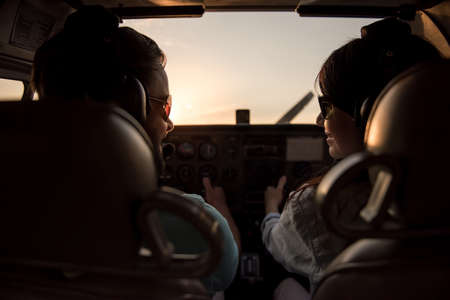 Back view from the inside of the plane, couple in aviation headsets is ready to fly