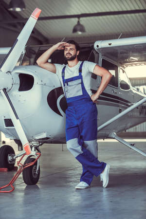 Full length portrait of handsome bearded mechanic in uniform looking away and leaning on the aircraft in hangar Stock Photo