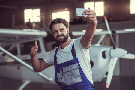 Handsome bearded mechanic in uniform is doing selfie using a smart phone and smiling while standing near an aircraft in hangar Stock Photo