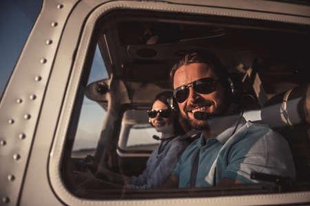 航空ヘッドセットの美しいカップルは、飛行する準備ができて航空機に座っている間、カメラと笑顔を見ています