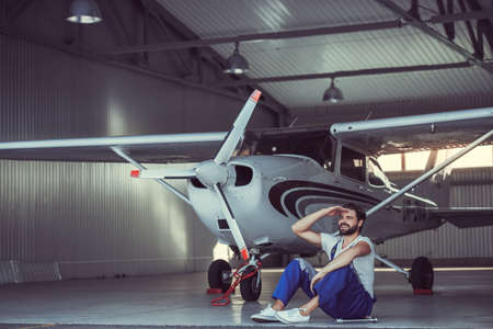 Handsome bearded mechanic in uniform looking away and sitting on the floor of hangar near the aircraft