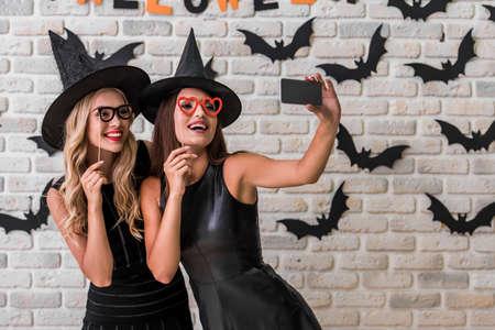黒ドレスと魔女の帽子の美しい女の子のパーティーの小道具を保持、ハロウィーンの装飾の背景にスマート フォンを使用して selfie をやって 写真素材