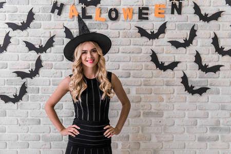 Het mooie blondemeisje in zwarte kleding en heksenhoed bekijkt camera en glimlacht, op achtergrond die voor Halloween wordt verfraaid