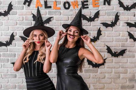 Mooie meisjes in zwarte jurken en heksenhoeden maken snorren van hun haar, kijken naar de camera en glimlachen, op achtergrond versierd voor Halloween