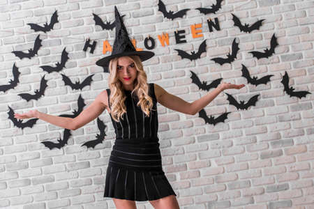 Beautiful blonde girl in black dress and witch hat is looking threateningly at camera, on background decorated for Halloween