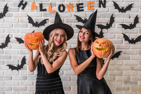 Beautiful girls in black dresses and witch hats are holding scary pumpkins, looking at camera and smiling on background decorated for Halloween