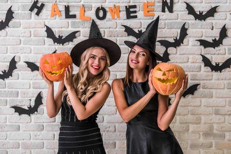 Schöne Mädchen in schwarzen Kleidern und Hexenhüten halten gruselige Kürbisse, betrachten Kamera und lächelt auf den Hintergrund, der für Halloween verziert wird