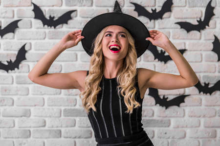 Beautiful blonde girl in black dress and witch hat is posing at camera, on background decorated for Halloween Stock Photo