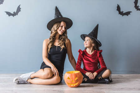 Cute little girl and her mom dressed for Halloween party and with accessories are looking at each other and smiling while sitting on the floor