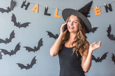 Beautiful young woman in witch hat is talking on the mobile phone and smiling, on background decorated for Halloween Stock Photo
