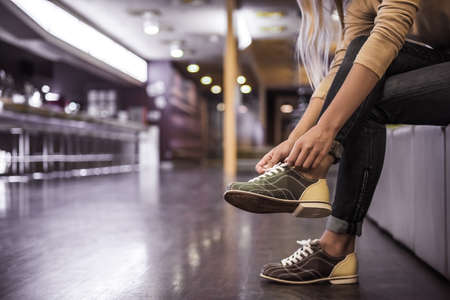 Cropped image of young woman lacing up bowling shoes ready to play bowling