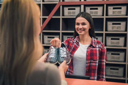 Beautiful girl is offering a pair of bowling shoes to the client and smiling