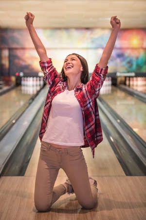 Beautiful girl is raising hands in fists and smiling while standing on her knees on bowling alley