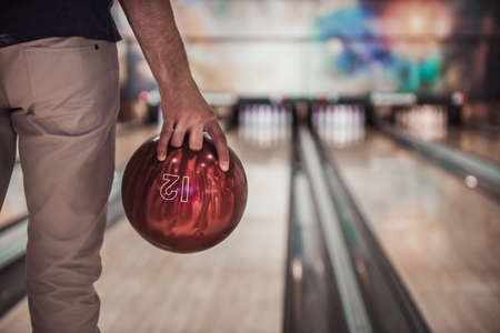 Cropped image of man holding a red bowling ball ready to throw it