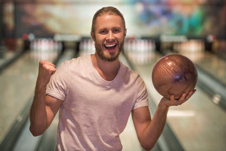 Handsome young man is holding a bowling ball, looking at camera and smiling ready to play bowling