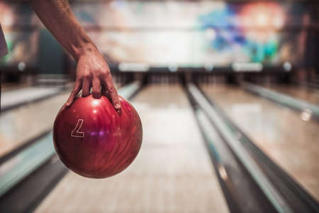 Man's hand holding a red bowling ball ready to throw it 写真素材