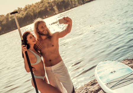 Beautiful young couple is doing selfie using a smart phone other and smiling; going to stand up paddle boarding Stock Photo