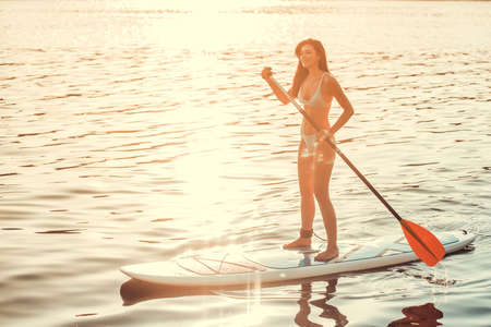 Beautiful young woman is smiling while SUP surfing on the river
