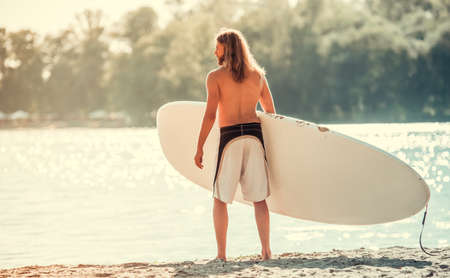 Handsome young man is holding a paddle board while standing on the beach