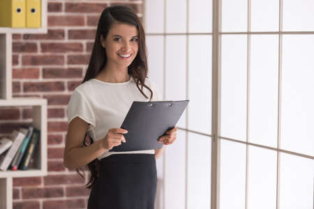 Beautiful young dark-haired woman is holding a folder, looking at camera and smiling while standing in office