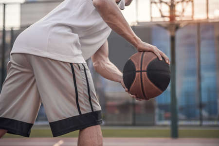 Cropped image of basketball player playing on basketball court outdoors